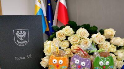 Na zdjęciu białe róże, kolorowe pierniczki w kształcie sówek oraz okładka dyplomu