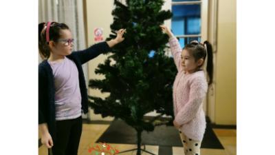 na zdjęciu dwie dziewczynki stojące przed choinką w przedszkolu