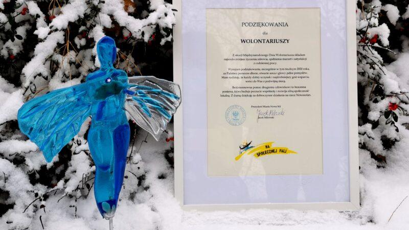 szklany anioł na tle śniegu i jarzębiny oraz dyplom z podziękowaniem dla wolontariuszy z okazji międzynarodowego dnia wolontariusza