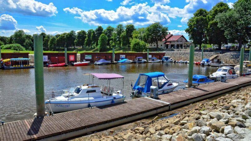 fragment nowosolskiej mariny. na pierwszym planie trap drewniany, za nim na rzece małe łodzie motorowe, w tle drzewa i budynek restauracji. jest lato, świeci słońce, na niebie pojedyncze chmury