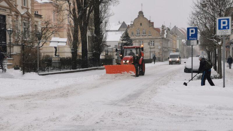 zima w mieście, skrzyżowanie ulic Muzealnej i Wróblewskiego. Po lewej stronie Muzeum Miejskie, w tle drogi pług który odśnieża, po prawej stronie człowiek z łopata odśnieża chodnik