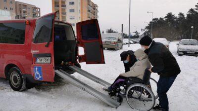 po lewej stronie fragment samochodu przystosowanego do transportu osób z niepełnosprawnością ruchową. Drzwi samochodu są otwarte, dwóch mężczyzn próbuje wciągnąć kobietę na wózku do samochodu. Jest zima, wszędzie leży śnieg. W oddali bloki mieszkalne, po prawej stronie las.