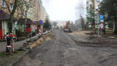 widok fragmentu ulicy na osiedlu Fredry w trakcie przebudowy. W tle widoczne maszyny budowlane. Po lewej stronie blok mieszkalny.