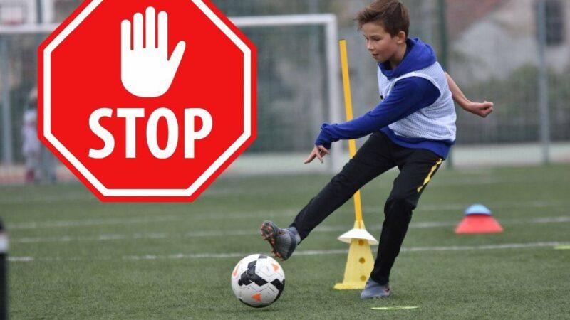 chłopiec kopiący piłkę, obok znak stop