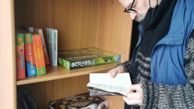 pan Czarek podopieczny noclegowni. Mężczyzna ma na sobie okulary,stoi przy regale z książkami i grami, czyta książkę
