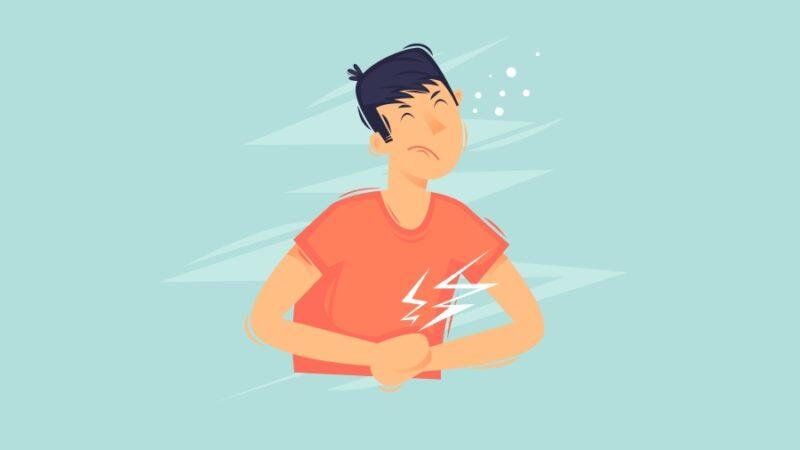 Grafika przedstawia młodego mężczyznę trzymającego się za brzuch. Mina wskazuje na to, że odczuwa ból.